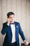 groom calls by telephone leaning other hand about a chair Stock Images
