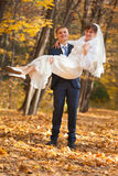 Groom carries his bride Stock Photos