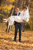 Groom carries his bride Stock Photos