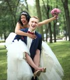 Groom carries his bride on the back in the Park. Outdoors stock images