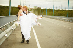 Groom carries his bride in his arms on bridge Royalty Free Stock Image