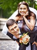 Groom carries his bride over back. Royalty Free Stock Photography