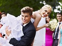 Groom carries his bride over shoulder. Royalty Free Stock Images