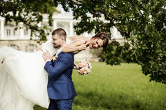 Groom carries his bride over shoulder Stock Images