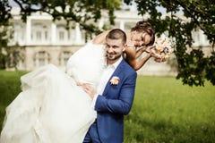 Groom carries his bride over shoulder Stock Photos