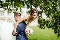 Groom carries his bride over shoulder Stock Photo