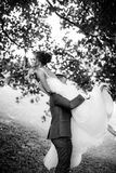 Groom carries his bride over shoulder Royalty Free Stock Photo
