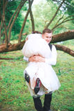 Groom carries his bride over shoulder. Outdoor. Royalty Free Stock Photo