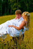 Groom carrying bride. Close up of groom carrying smiling bride through meadow in countryside Stock Photo