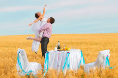Groom is carrying bride on arms Royalty Free Stock Image