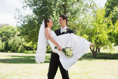Groom carrying bride in arms at garden Stock Image
