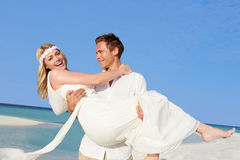 Groom Carrying Bride At Beautiful Beach Wedding. Smiling Stock Photo
