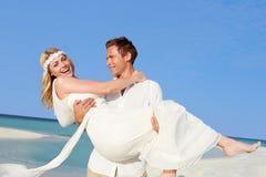 Groom Carrying Bride At Beautiful Beach Wedding Stock Photo
