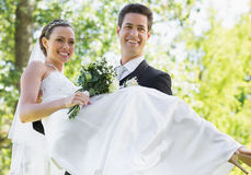 Groom carrying bride in garden Royalty Free Stock Image
