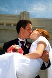Groom carrying bride and kissing her Stock Photos