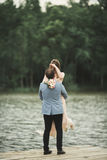 Groom carrying bride near lake and forest Royalty Free Stock Images