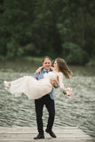 Groom carrying bride near lake and forest Stock Images