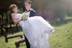 Groom carrying bride outdoors royalty free stock photos