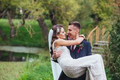 Groom carrying his beautiful bride. Royalty Free Stock Photos