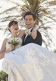 A groom carrying his bride Royalty Free Stock Images