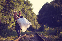 Groom carrying his bride on a railroad Royalty Free Stock Photo