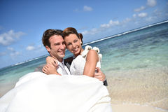 Groom carrying his wife in the arms Stock Image