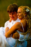 Groom carrying smiling bride. Half body portrait of groom carrying smiling bride in his arms Royalty Free Stock Photos