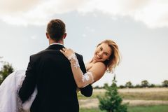 Groom carrying smiling bride on wedding day Royalty Free Stock Images
