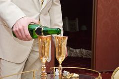 Groom and champagne. Groom pours a glass of champagne Royalty Free Stock Images
