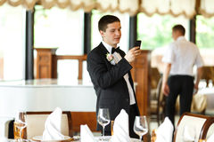 Groom checks his phone while he waits in a restaurant's hall.  Royalty Free Stock Images