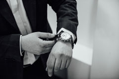 Groom clasping stylish watch band on his wrist.  Royalty Free Stock Image