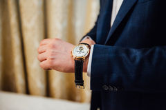 Groom clasping stylish watch band on his wrist Stock Image