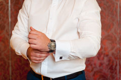 Groom clasping stylish watch band on his wrist Stock Photography
