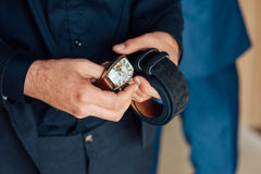 Groom clasping stylish watch band on his wrist Stock Images
