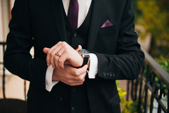 Groom clasping stylish watch band on his wrist Stock Photo