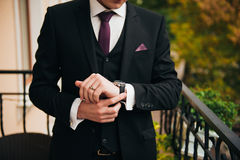 Groom clasping stylish watch band on his wrist.  Stock Photography