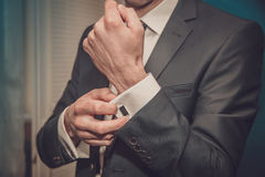 Groom clasps cuff links on a shirt sleeve close up stock photo