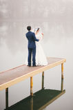 Groom corrects  veil for  bride standing on  pier Stock Photos