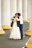 Groom covering brides shoulders with jacket and kissing her Stock Image
