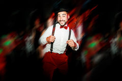 The groom dancing on dance floor, moving in motion. Cheerful man wearing hat and bow tie with suspenders. Wedding color Royalty Free Stock Photos