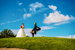 Groom dancing upside down on blue sky Stock Photo