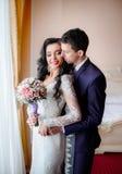 Groom in dark blue suit hugs pretty bride with black curls Royalty Free Stock Image