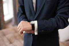 The groom in dark suit puts on a watch, closeup Royalty Free Stock Image