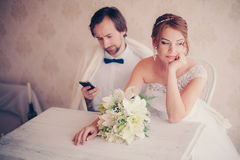 Groom is distracted with the phone at wedding photosession Royalty Free Stock Photography