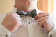 Groom doing a Bowtie adjustment Stock Images