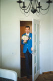 Groom at Doorway. Groom with wedding bouquet opening door Royalty Free Stock Photo