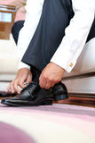 Groom dresses and binds shoes Stock Images