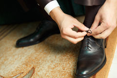 Groom dresses and binds shoes Royalty Free Stock Photo