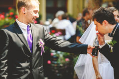 Groom drinks soda from a bottle held by his friend Royalty Free Stock Images