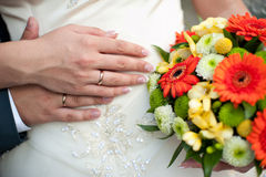 Groom embraces the bride, the bride holds a wedding bouquet Stock Photo
